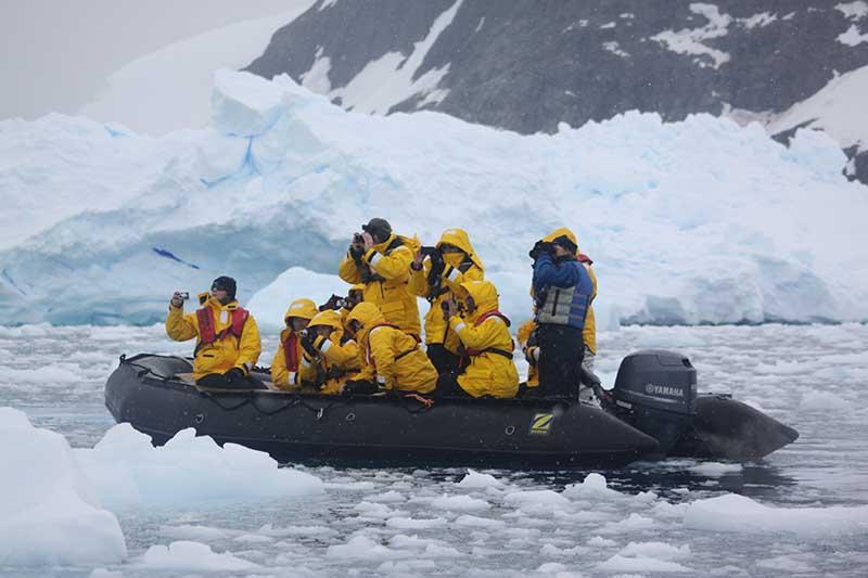Des croisiéristes en zodiac explorant l'Antarctique